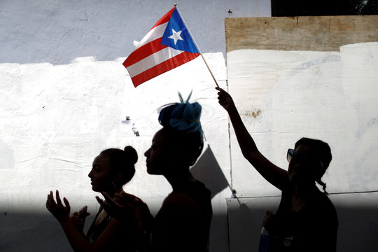 A woman waves a Puerto Rican flag during ongoing protests calling for the resignation of Governor Ricardo Rossello in San Juan