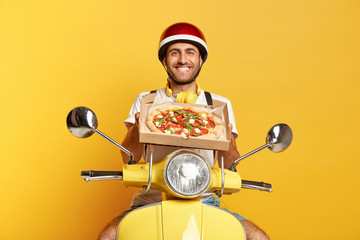 Foto auf Acrylglas Pizzeria Satisfied motorcyclist delivers tasty fresh baked pizza, wishes good appetite for customers, holds cardboard box, wears protective helmet, sits on fast motorbike, isolated on yellow studio wall