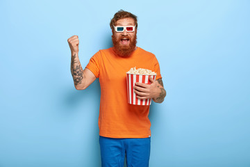 Joyful redhead man spectator watces 3d film, wears special glasses, spends free time at cinema, clenches fist, laughs excitedly, poses indoor. Leisure, hobby, entertainment and people concept