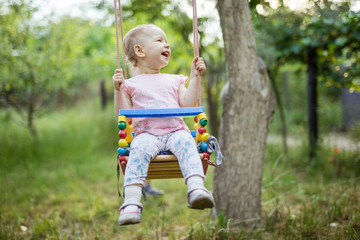 Happy little girl on swing in summer garden
