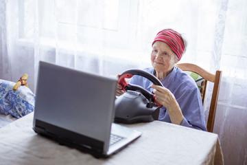 Senior woman enjoying car racing video game on laptop at home
