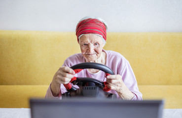 Senior woman enjoying car racing video game on laptop while sitting on couch