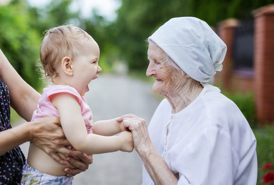 Happy toddler girl and her great grandmother holding hands and looking at one another