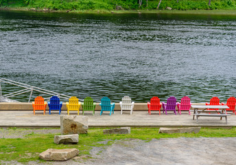 Colorful Wood Adirondack Chairs Lined Up on a Dock Overlooking a River