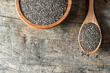 Chia seeds ( Salvia Hispanica ) in wooden spoon and bowl on wooden rustic background. Cereal healthy food contains omega 3, a dietary supplement gluten free