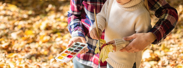 Girl and her mother enjoy autumn season. Drawing with paint autumn leaves outside