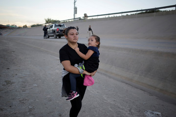 Migrant woman and her daughter move away from members of the Mexican National Guard at Rio Bravo river before crossing illegally into El Paso, Texas, U.S. as seen from Ciudad Juarez