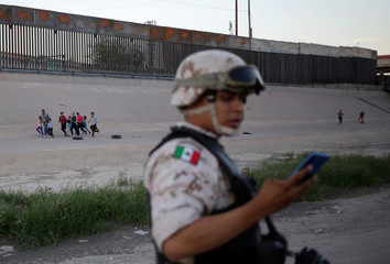 Migrants are seen running along the banks of the Rio Bravo river near a member of the Mexican National Guard after crossing illegally into El Paso, Texas, U.S. as seen from Ciudad Juarez
