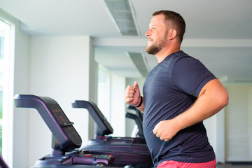 full male runs on a treadmill in a gym. concept of weight loss and sport. side view.