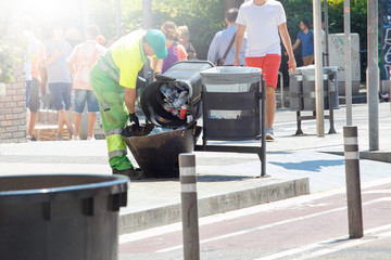 A professional cleaner works on a city street. Worker cleaning trash on street.