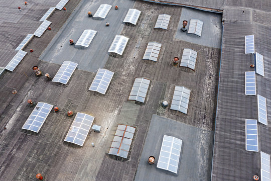 distribution warehouse roof from above. ventilation systems are installed on the roof with skylights