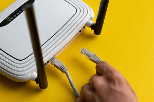 hand conncecting the ethernet wire cable with wi-fi remote point