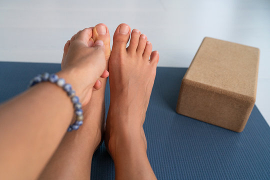 Yoga stretches big toe pull stretch exercises woman doing hamstring stretching at home on fitness mat training stretching legs touching toes. Hand wearing mala bracelet with yoga block.