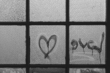 An old window with glass pane and the lettering Love