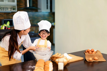 Happy asian family in the kitchen.Mother and son help to make cake.Mom teaching boy cooking bread dough.Sweet cute boy is learning how to make a cake in the kitchen. Fototapete