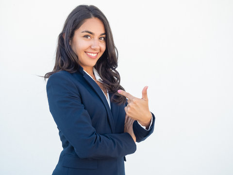 Cheerful female professional proud of herself. Happy beautiful black haired young woman in formal suit pointing index finger at herself. Self confidence concept
