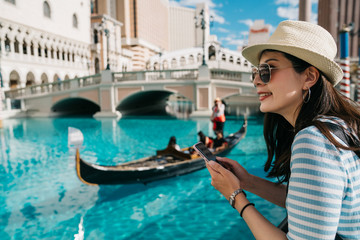 Keuken foto achterwand Venetie Tourist woman travel in Italy. View on Grand canal with gondola boat sailing and moving on it. Young girl with straw hat and sunglasses smiling using mobile phone while relax enjoy view in venice.