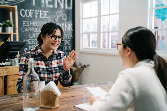 Happy smiling millennial female applicant being interviewed by hr manager in coffee store. recruiting woman reading resume of positive funny graduate girl looking for first job. good impression
