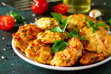 Chicken cutlets made from minced meat close-up, with paprika, tomatoes and greens in a bowl on a dark stone table.
