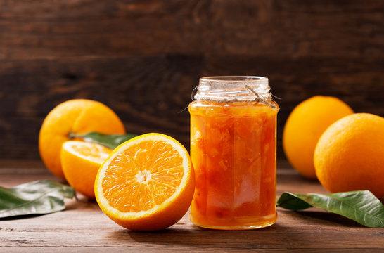 glass jar of orange  jam with fresh fruits