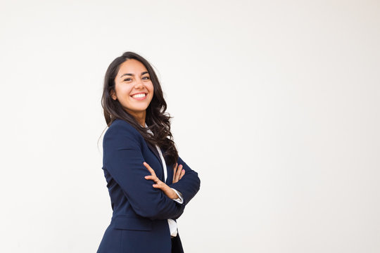 Young businesswoman smiling at camera. Portrait of beautiful happy young woman standing with crossed arms and looking at camera isolated on grey background. Emotion concept