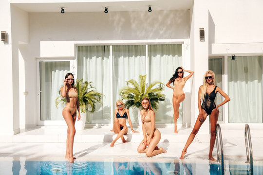 beautiful sexy women in elegant swimming suits relaxing near swimming pool at white villa