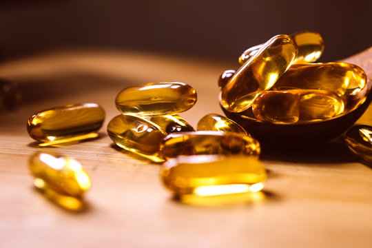Close up the vitamin D and Omega 3 fish oil capsules supplement on wooden plate for good brain , heart and health eating benefit