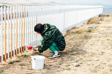 Beautiful girl paints a wooden fence with a brush