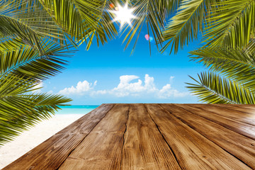Table background with wooden board in the beautiful ocean and beach view. Palm leaves and clear...