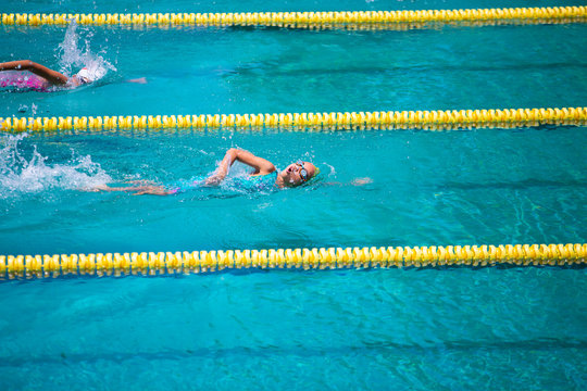 Athlete in freestyle swimming race in swimming pool