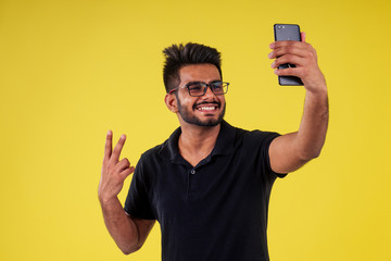 smiling handsome india man photographing selfie in studio yellow background