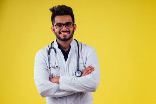 indian male doctor wearing glasses and white cloak in yellow background studio