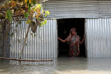 Saju Begum, a flood-affected woman poses for a picture inside her house in Jamalpur