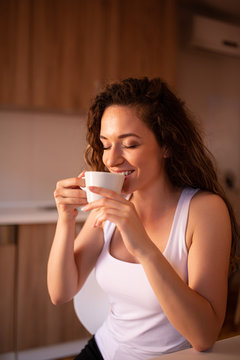 Young woman enjoying morning coffee at home, portrait.