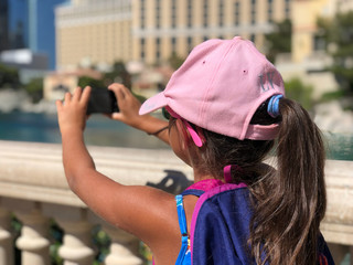 Young girl taking pictures of Las Vegas on a sunny day