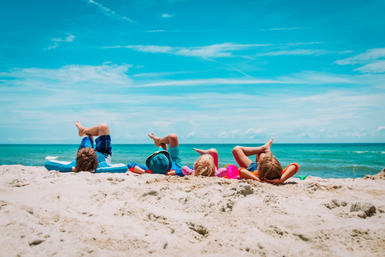 father with son and daughters relax on beach