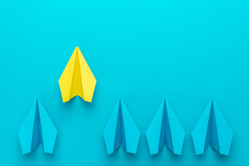 Top view of yellow paper plane as out of the crowd concept over turquoise blue background with copy space. Flat lay image of paper plenes as leadership concept. Leaving the crowd metaphor.