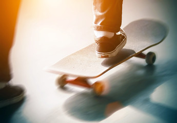 The guy in jeans and sneakers quickly pushes his foot off the asphalt and rides a skateboard, illuminated by bright sunlight. The picture shows the speed and dynamics of what is happening.