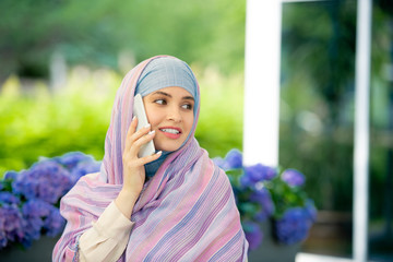 Young successful muslim businesswoman in hijab consulting someone on smartphone