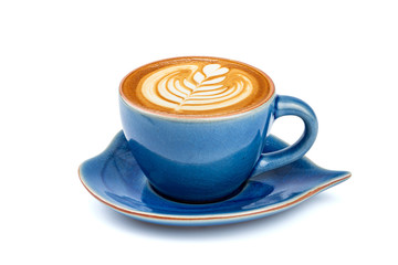 Side view of hot latte coffee with latte art in a ceramic blue cup and saucer isolated on white background with clipping path inside.