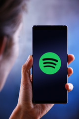 Woman holding smartphone displaying logo of Spotify