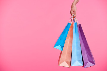 Four colorful paperbags held by hand of female shopaholic