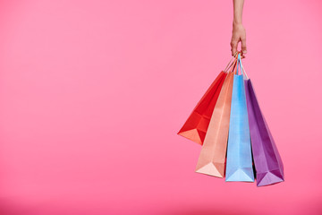 Hand of shopper holding bunch of colorful paperbags