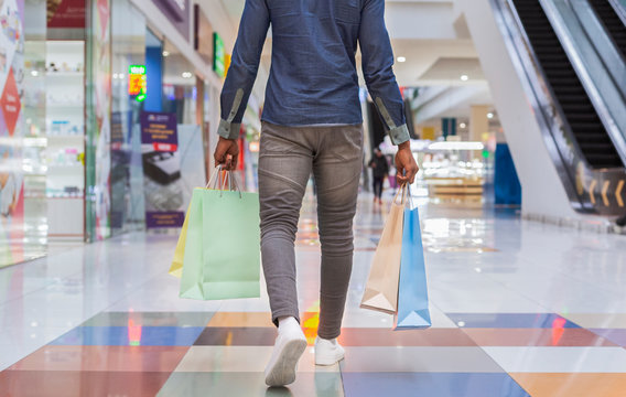 African american man walking with shopping bags