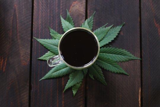 Closeup shot o cannabis, hemp, CBD or THC infused black coffee on dark wood background