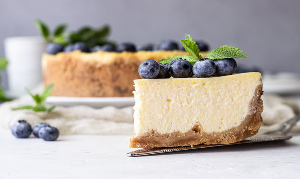 New York style cheesecake, fresh blueberries and mint on a white plate. Light stone background. Copy space.