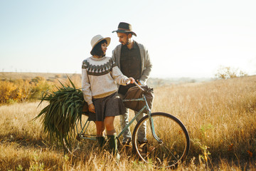 Lovely hipster couple with bike . Couple wearing beautiful hats and sweaters. Lifestyle, happy couple of two play on a sunny day in the park. The concept of youth, love and lifestyle. Sunset in autumn