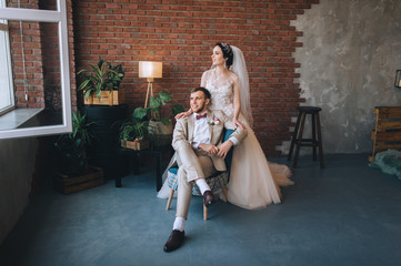 Stylish groom gently hugs a beautiful brunette bride against the background of a brick wall. Wedding portrait of newlyweds in love in a modern studio with a beautiful interior. Conceptual photography.