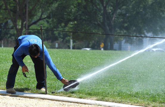 A passerby attempts to cool off by soaking his cap with spray from a water sprinkler on the National Mall during a heat wave, in Washington,DC