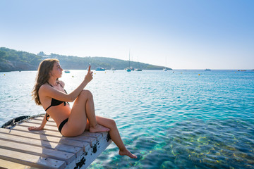 Ibiza girl taking smartphone photos Wall mural